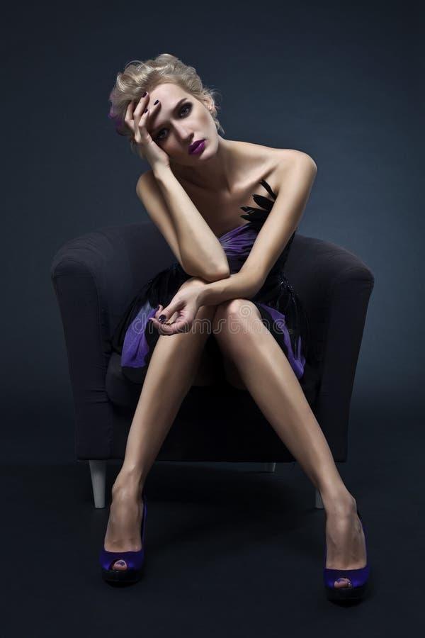 美丽的椅子豪华坐的妇女 免版税库存照片