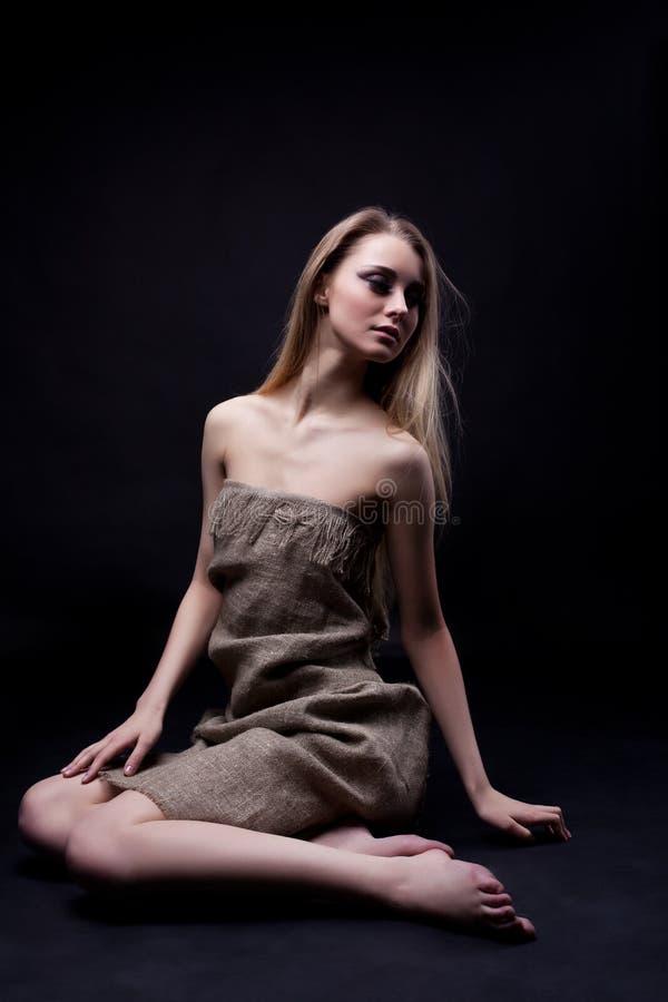 美丽的楼层坐的妇女年轻人 免版税库存照片