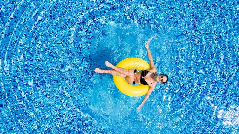 美丽的概念池假期妇女年轻人 亭亭玉立的少妇顶视图比基尼泳装的在大游泳池的黄色空气可膨胀的圆环 库存照片
