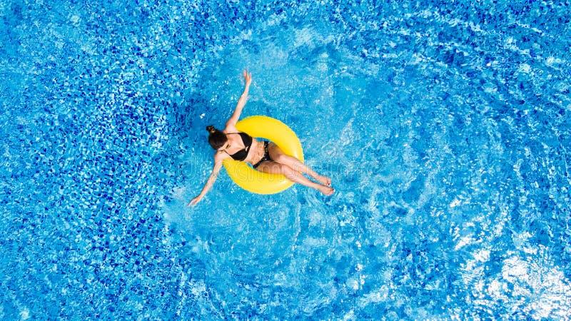 美丽的概念池假期妇女年轻人 亭亭玉立的少妇顶视图比基尼泳装的在大游泳池的黄色空气可膨胀的圆环 免版税库存照片