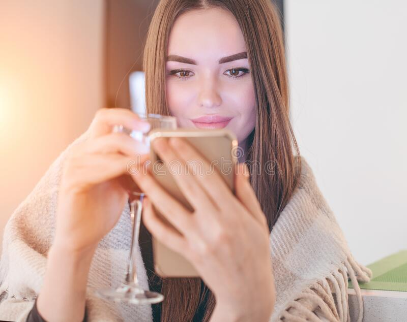 美丽的模特时装女孩,在家喝红酒,看着她的智能手机,微笑着 饰有花饰的美女 免版税图库摄影
