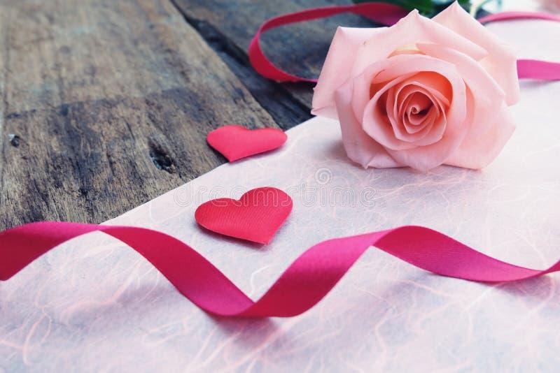 美丽的橙色桃红色玫瑰和深红缎心脏Valentine&的x27;s背景 免版税库存图片
