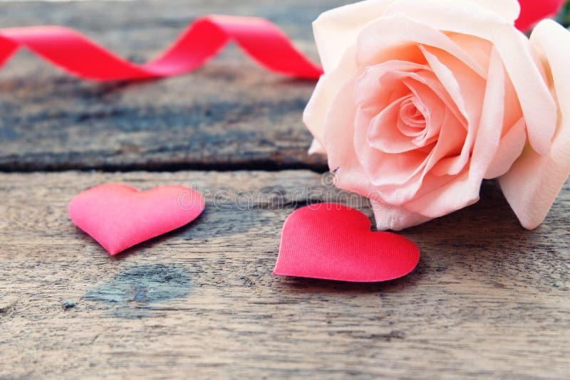 美丽的橙色桃红色玫瑰和深红缎心脏Valentine&的x27;s背景 库存照片