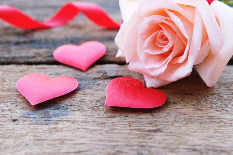 美丽的橙色桃红色玫瑰和深红缎心脏Valentine&的x27;s背景 免版税库存照片