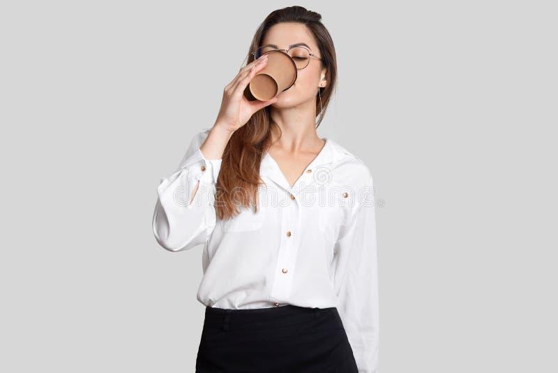 美丽的欧洲妇女饮料咖啡射击的腰部,穿戴在白色女衬衫和黑裙子,有咖啡休息在工作,pos以后 库存图片
