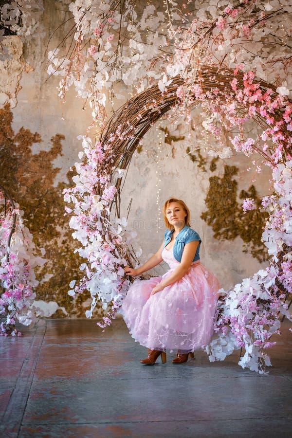 美丽的正面妇女在春天有花的区域在演播室 库存图片