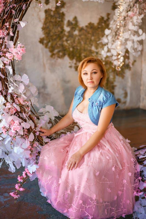 美丽的正面妇女在春天有花的区域在演播室 免版税库存图片