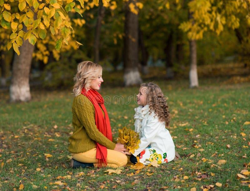 美丽的母亲和女儿在户外五颜六色的秋天 库存图片