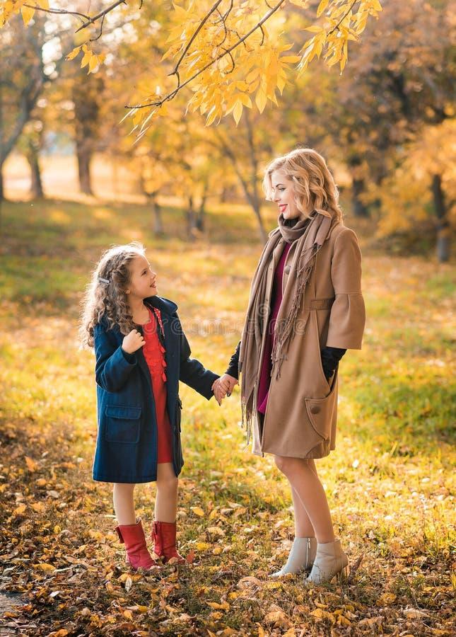 美丽的母亲和女儿在户外五颜六色的秋天 图库摄影