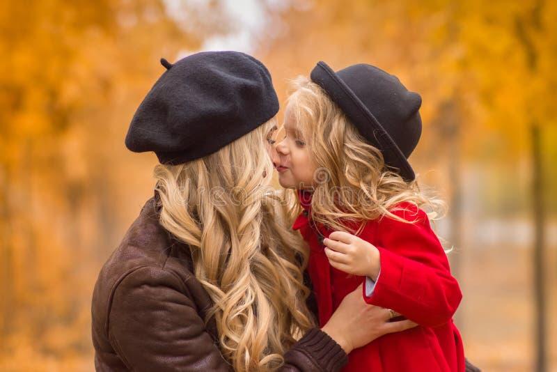 美丽的母亲和女儿秋天庭院背景的轻轻地互相拥抱 库存图片