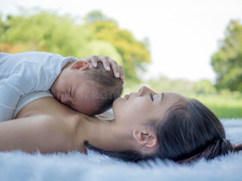 美丽的母亲和她的一起睡觉在公园、医疗保健和医疗爱的儿子婴孩 免版税库存图片