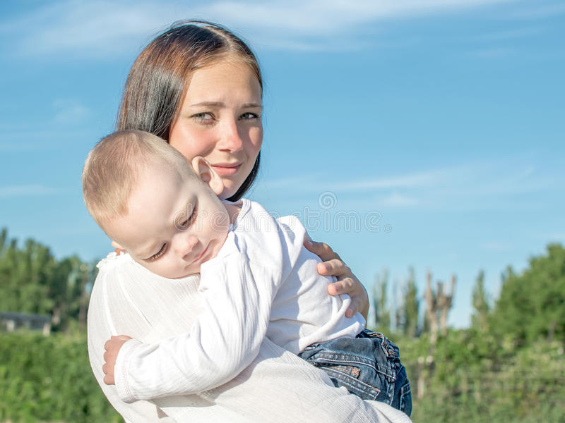 年轻美丽的母亲和拥抱在自然的男婴在夏天 抱她的胳膊的俏丽的妇女睡觉的孩子 免版税库存照片