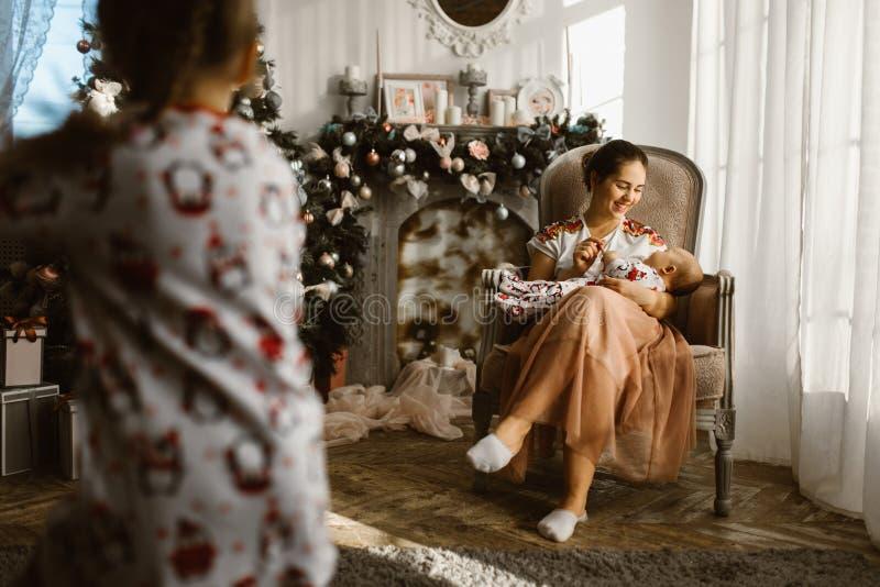 美丽的母亲在有她的小婴孩的扶手椅子其次坐 免版税图库摄影