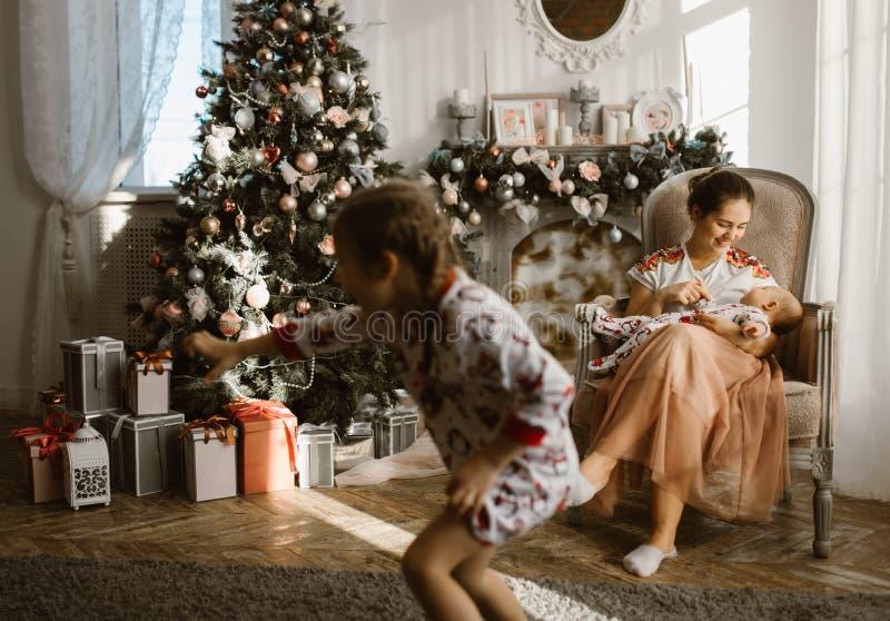 美丽的母亲在有她的小婴孩的扶手椅子在壁炉旁边和与礼物的新年的树坐在 免版税库存照片