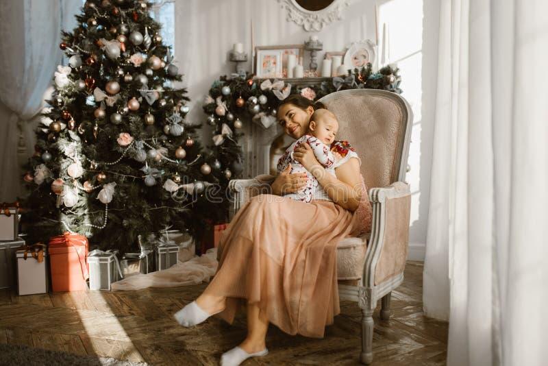 美丽的母亲在有她的小婴孩的扶手椅子在壁炉旁边和与礼物的新年的树坐在 库存照片