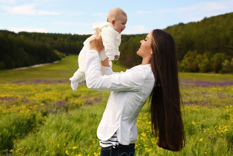 美丽的母亲获得与她的小逗人喜爱的婴孩的乐趣在夏天庭院 免版税库存图片
