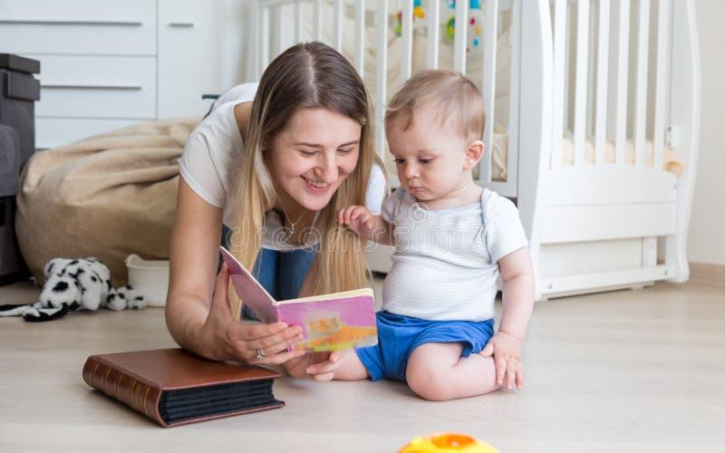 美丽的母亲阅读书画象对她的男婴的 免版税库存图片