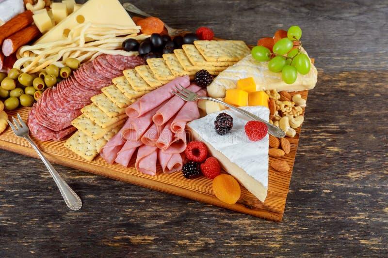 美丽的汇集集合装饰绿橄榄、无花果、坚果和莓果在新被分类的乳酪构成 免版税库存图片