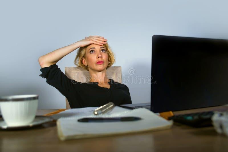 美丽的沮丧和哀伤的白肤金发的妇女与便携式计算机感觉被用尽的和生气开会一起使用在办公桌淹没 库存图片