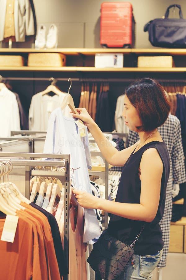 美丽的泰国妇女亚洲女孩购物衬衣 免版税图库摄影