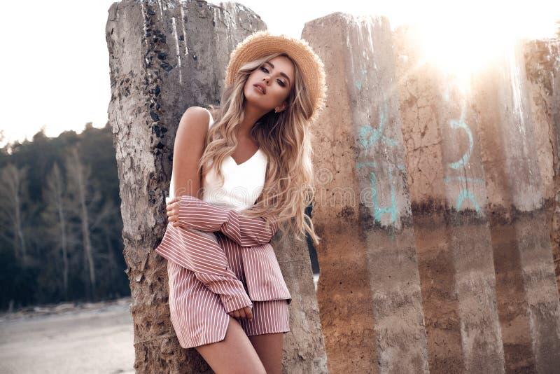 美丽的浪漫女孩在草帽在阳光下摆在 乡下风景,在背景的森林自然 o 免版税库存照片