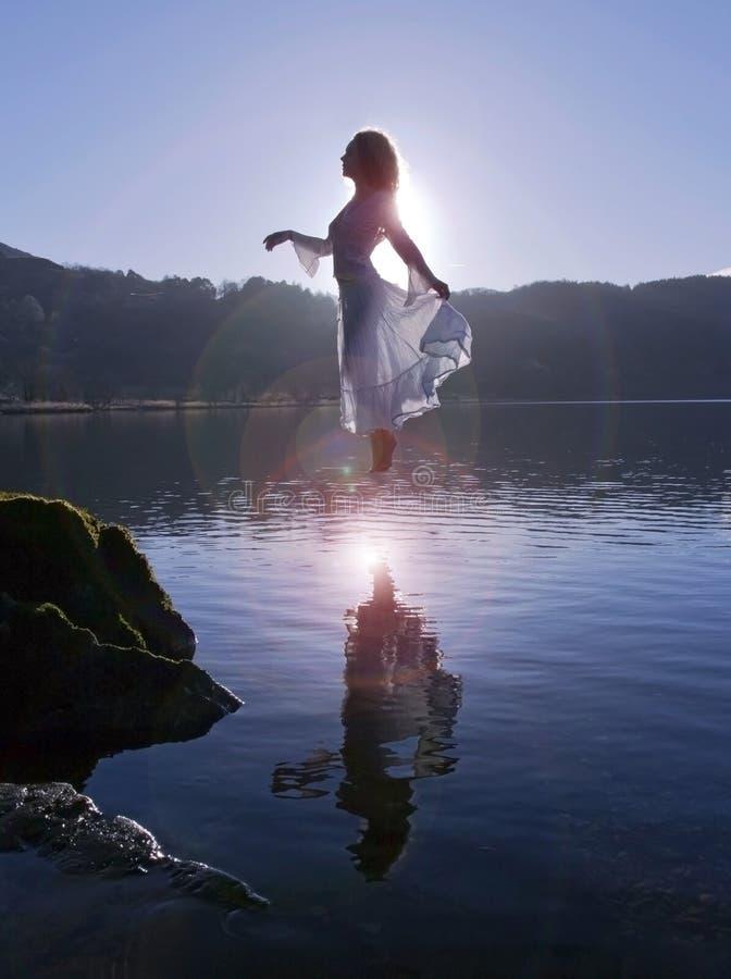 美丽的浮动女孩在白色穿戴了,现出轮廓由在寂静的湖反映的太阳 免版税库存照片