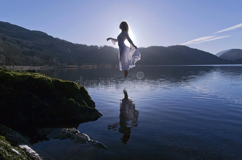美丽的浮动女孩在白色穿戴了,现出轮廓由在寂静的湖反映的太阳 库存图片