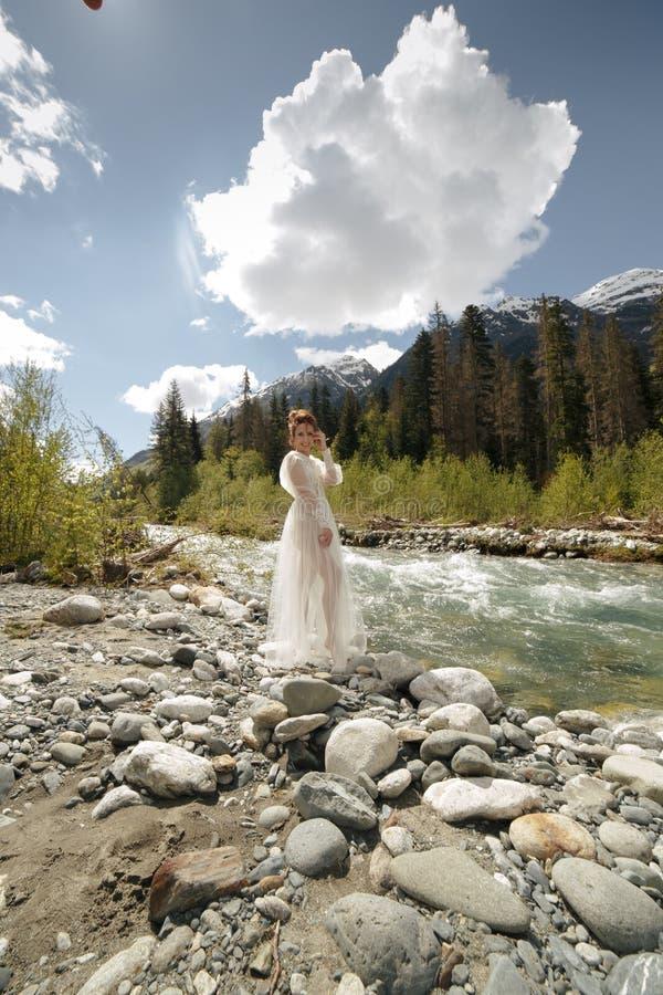 美丽的浴巾礼服的闺房性感的新娘 女孩时尚时髦与在北欧卡累利阿人的自然的花束 免版税图库摄影