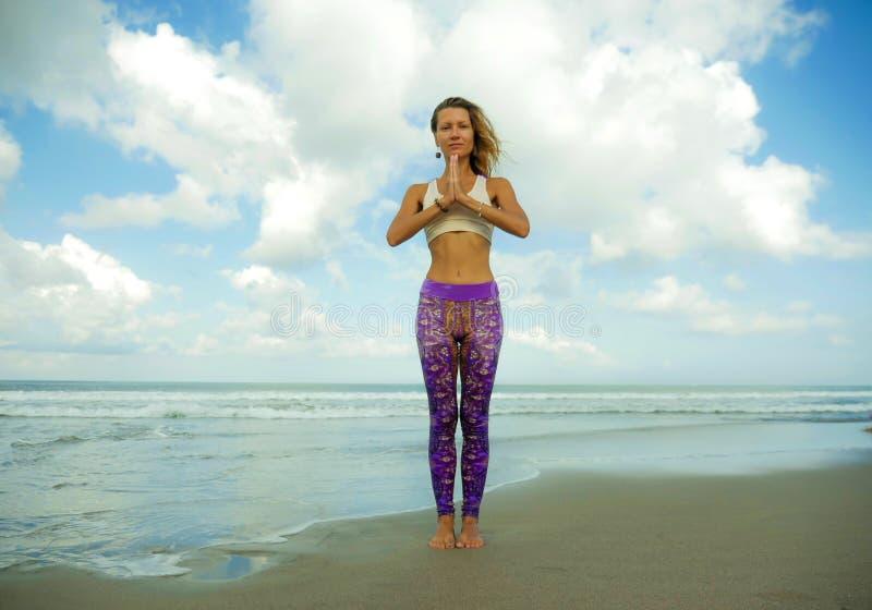 美丽的海滩的可爱和愉快的运动女孩在被集中和放松的瑜伽姿势做凝思锻炼户外  免版税库存照片