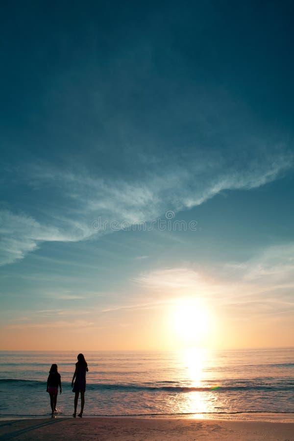 美丽的海滩的女孩在日落期间。 库存图片