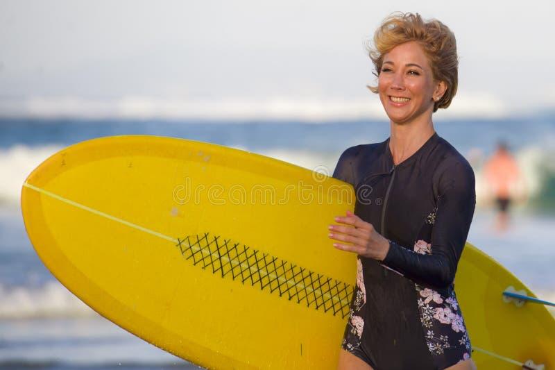美丽的海滩的年轻可爱和愉快的白肤金发的冲浪者女孩运载黄色水橇板从水走出去享受summ的 库存图片
