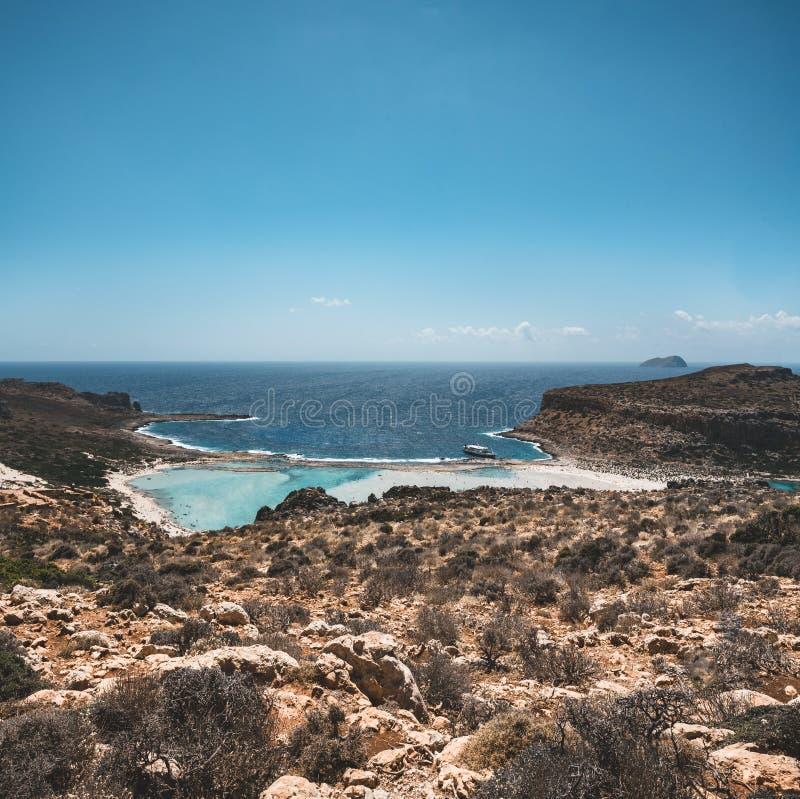 美丽的海滩的看法在Balos克利特的,希腊盐水湖和格拉姆武萨群岛海岛 晴天,与云彩的蓝天 免版税库存图片