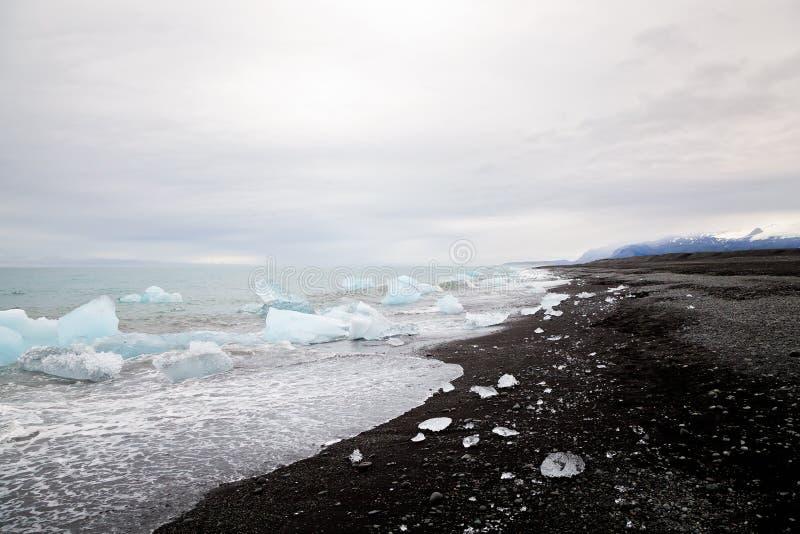 美丽的海滩在有黑熔岩沙子和iceber的南冰岛 免版税库存图片