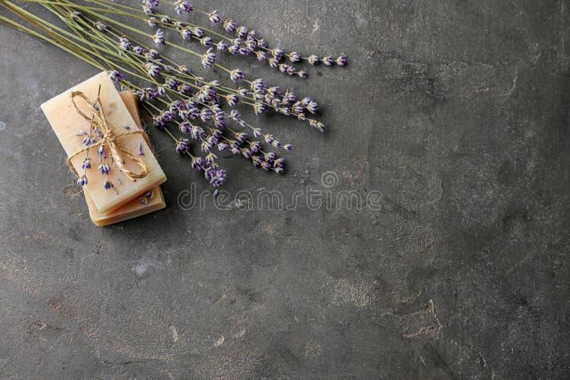 美丽的淡紫色和肥皂在黑暗的桌上 免版税库存照片