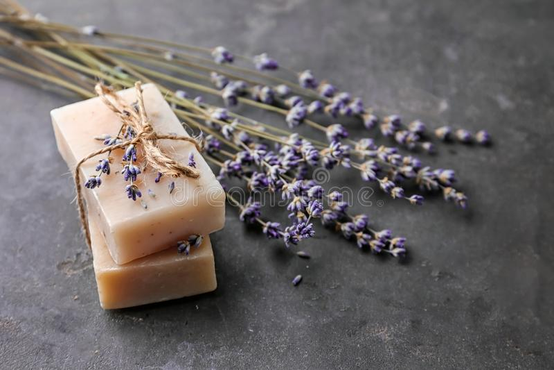 美丽的淡紫色和肥皂在黑暗的桌上 库存照片