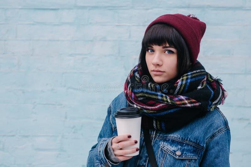 年轻美丽的深色的在一条冷的街道上的女孩饮用的咖啡 免版税库存图片