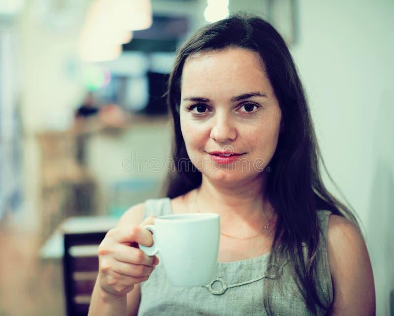 美丽的深色的在咖啡馆的女孩饮用的茶 免版税图库摄影