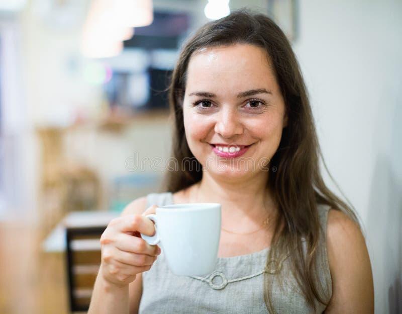 美丽的深色的在咖啡馆的女孩饮用的茶 免版税库存图片