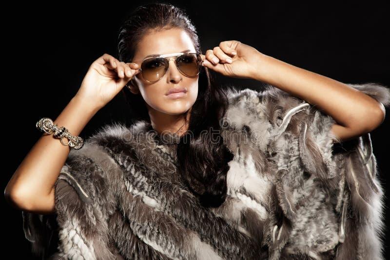 美丽的深色的夫人佩带的毛皮和太阳镜。 库存照片