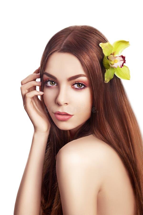 美丽的深色的女孩。 有兰花花的健康长的头发 免版税库存照片