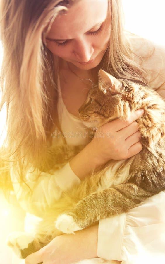 美丽的深色的女孩和她的姜猫 免版税库存照片