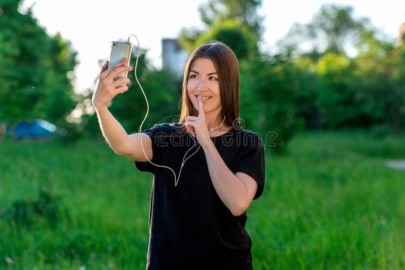 美丽的深色的女孩在室外的夏天 谈话在微笑的电话显示标志平静地打手势 听到音乐 免版税库存图片