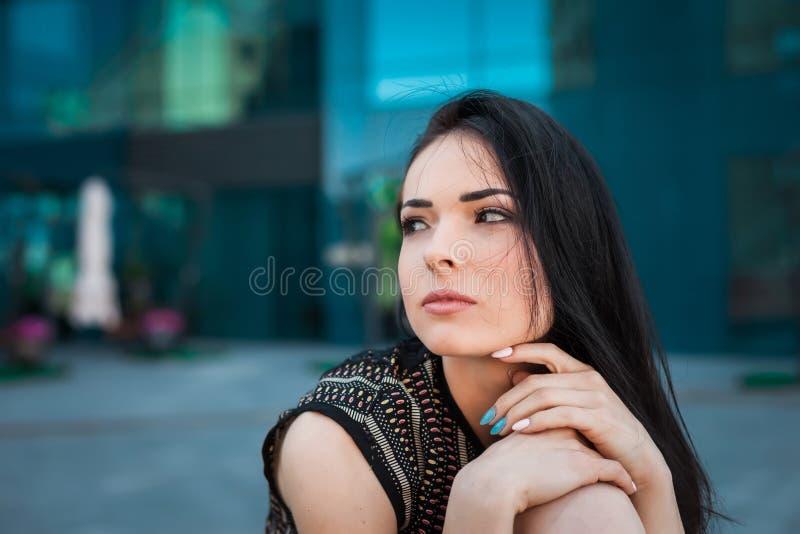 美丽的深色的女孩坐遏制 库存图片