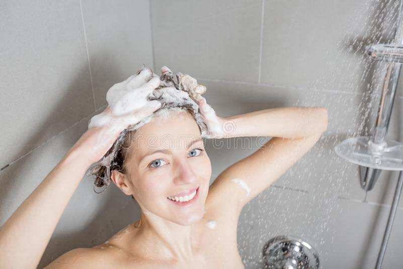 美丽的深色的女性淋浴头发长的模型多种族香波的阵雨飞溅洗涤液妇女 免版税库存照片