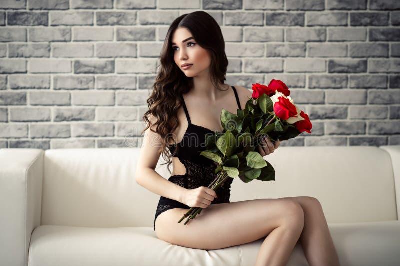 美丽的深色的妇女女用贴身内衣裤的和有玫瑰的在手上坐长沙发 库存图片