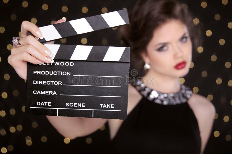 美丽的深色的妇女式样举行的影片拍手委员会戏院 库存照片