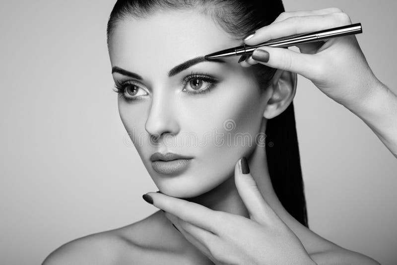 美丽的深色的妇女绘眼眉 图库摄影