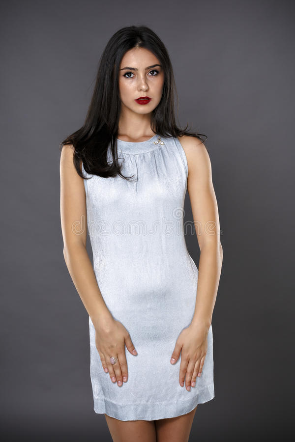 美丽的深色的妇女画象被隔绝的一件银色礼服的 免版税库存照片