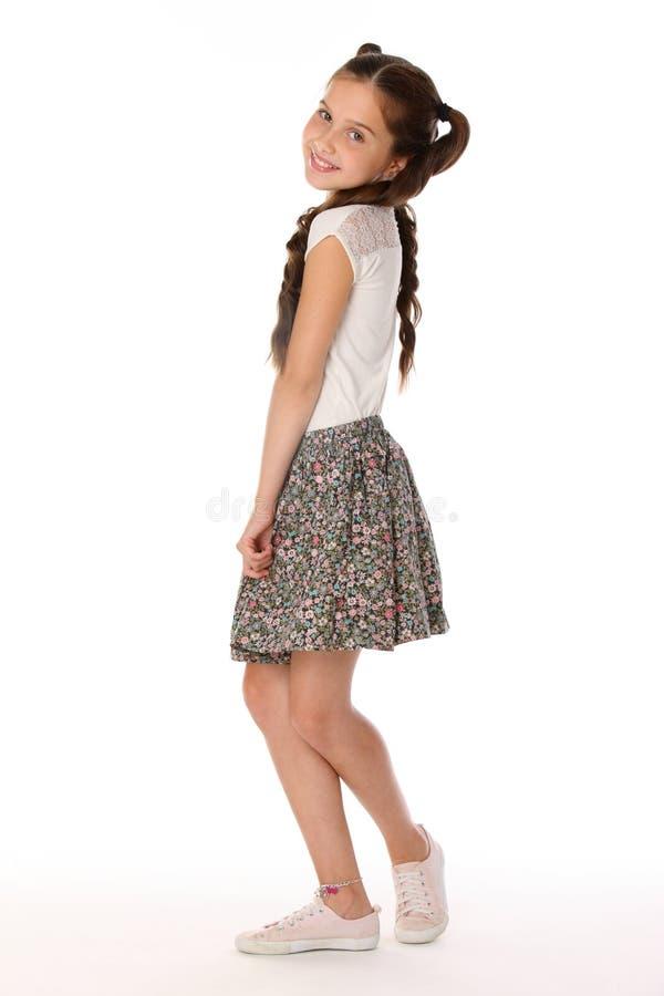 美丽的深色的小女孩摆在有光秃的腿的一条裙子的12岁 库存照片
