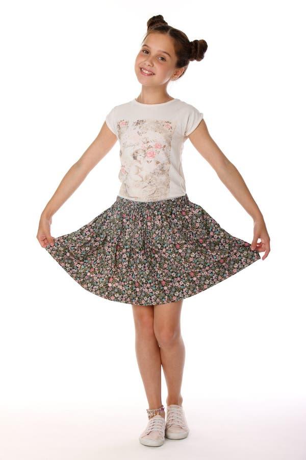 美丽的深色的小女孩摆在有光秃的腿的一条裙子的12岁 库存图片